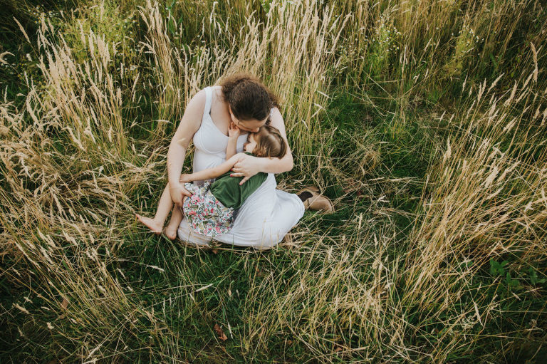 Pregnant mom tickles and snuggles her oldest daughter thinking about pregnancy the second time around in the tall grass in Hillsboro, Oregon