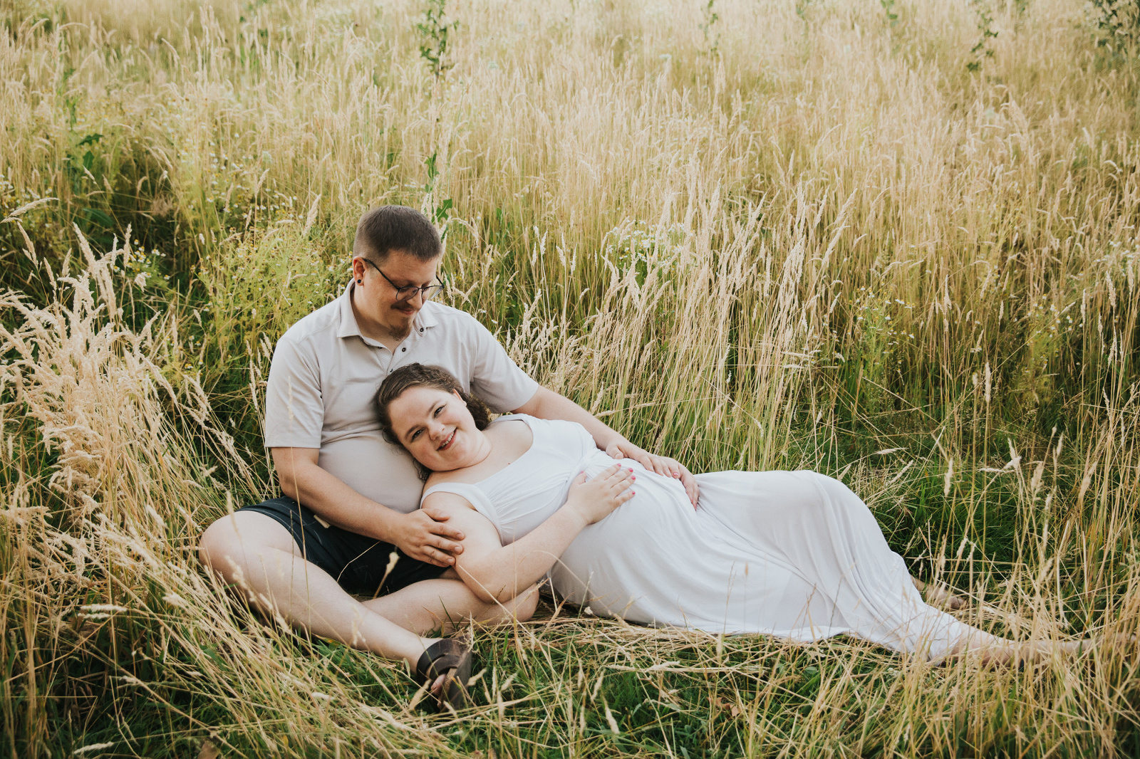 Dad/Partner looks on with affection at his wife who is pregnant the second time around in some tall grass in Hillsboro, Oregon.