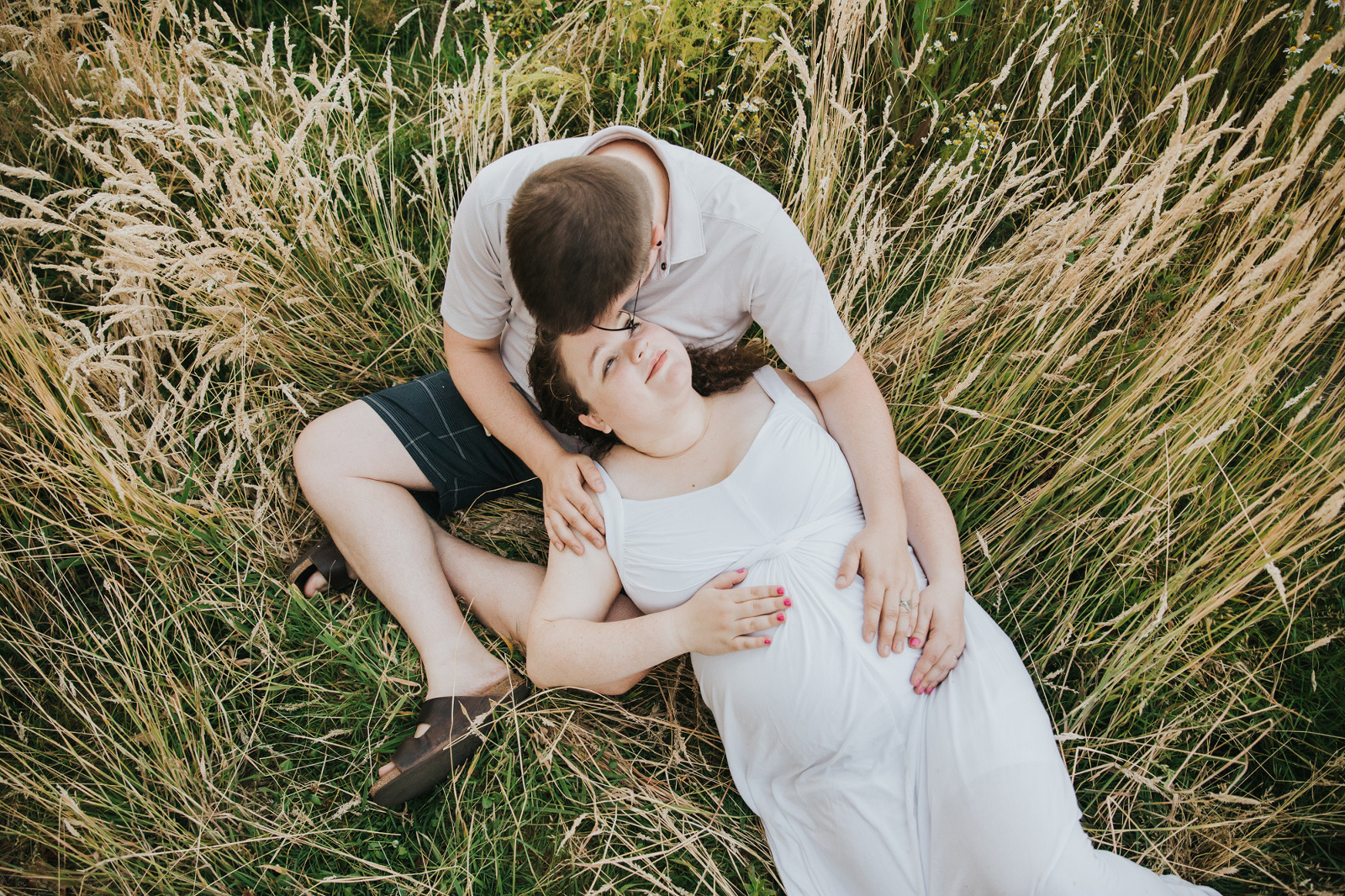 Pregnant mom, dad/partner, and oldest daughter snuggle and tickles in the grass during their maternity session in Hillsboro, Oregon